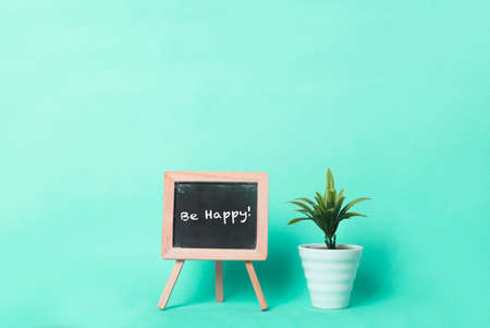Be happy text on a blackboard beside a plant in a pot. Plain turquoise background. Stock Photo