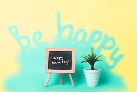 Happy Monday text on a blackboard beside a plant in a pot. Be happy text on plain turquoise background. Stock Photo