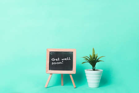 Get well soon text on a blackboard beside a plant in a pot. Plain turquoise background.