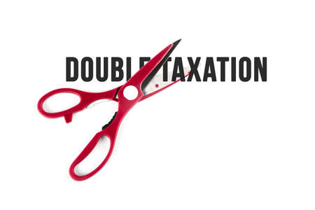 Scissor cutting text of double taxation. Isolated on white background.