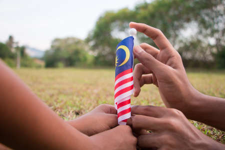 Independence Day concept - Kids' hands holding Malaysian flag on a field.