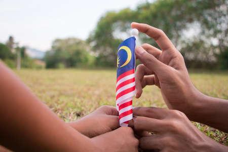 Unabhängigkeitstag-Konzept - Kinderhände, die malaysische Flagge auf einem Feld halten. Standard-Bild
