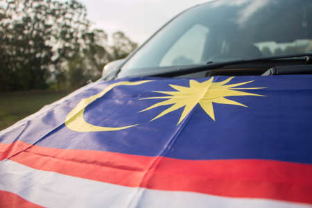 Independence Day concept - Malaysian flag on a Malaysian car. Stock Photo