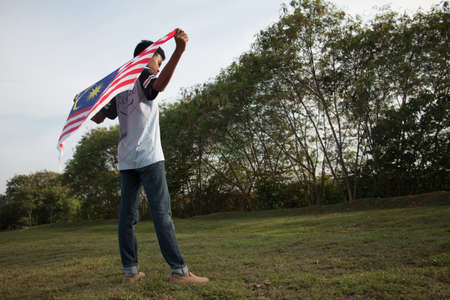 Independence Day concept. A happy and proud boy holding Malaysian flag. Sky background.