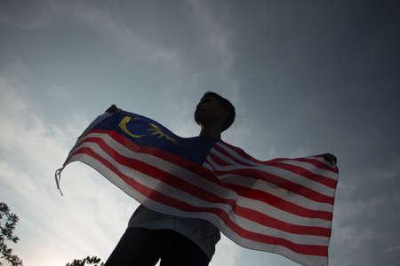 Konzept des Unabhängigkeitstags. Ein glücklicher und stolzer Bürger, der malaysische Flagge hält. Himmel Hintergrund.