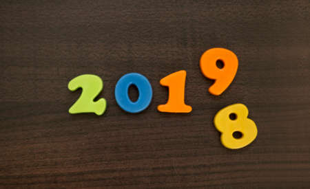 Year 2019 with number 8 falling down. End of year. New year is coming. Wooden background. Foto de archivo