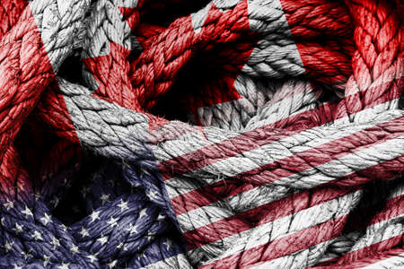 Country flags of Canada and United States of America USA in a rope shape. Concept of foreign or diplomatic relations between countries. 写真素材