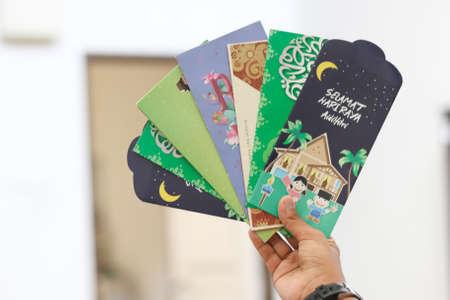"""Geldpaket als Hari Raya Geschenk für Ramadan und Eid al-Fitri Feier. """"Salam Aidilfitri"""" Text in Arabisch und Malaiisch übersetzt in Englisch als """"Eid al-Fitr"""""""