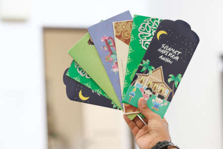 "Money packet as Hari Raya gift for Ramadan and Eid al-Fitri Celebration. ""Salam Aidilfitri"" text in Arabic and Malay translated in English as ""Eid al-Fitr"""