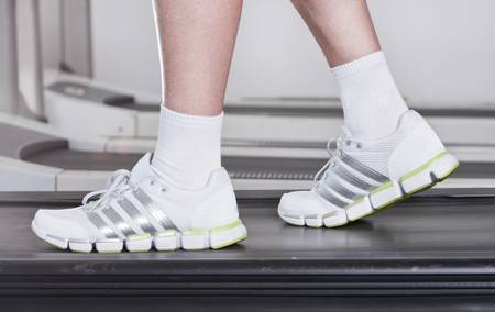 feet of the guy in sneakers on a racetrack in fitness club photo
