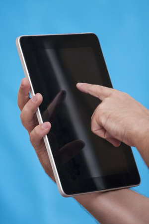 male hands holding a tablet touch computer gadget and touches the screen photo