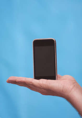 Cell phone with touchscreen in male hand on blue background photo