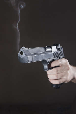 smoking gun after the shot in the hand of man