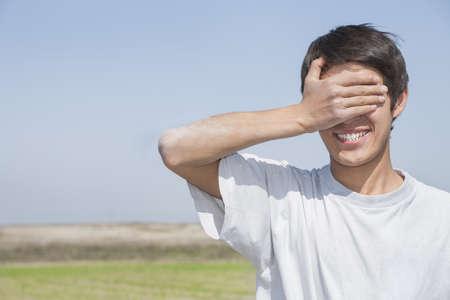 blindly: Una imagen de un hombre joven con la mano sobre sus ojos