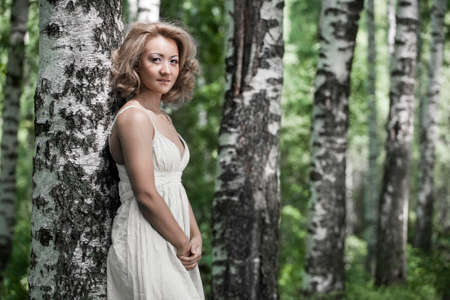 european white birch: portrait of beautiful young woman in white blouse standing and smiling at birch forest