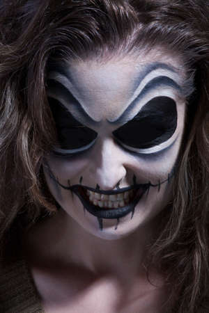 female vampire: Woman with face painting in dark room (Halloween)