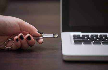 Hand pushing USB stick into laptop