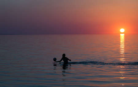 balonmano: silhouette of man at sunset in the lake with the ball