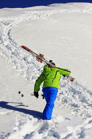 pila: Person with ski on shoulders is walking on the snow