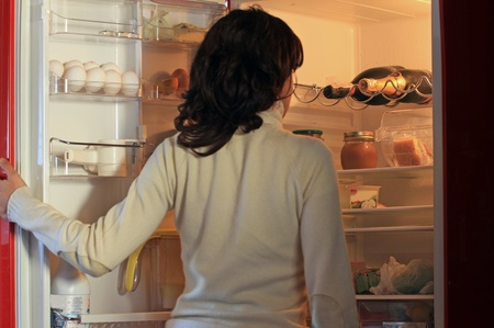 a girl is opening the fridge