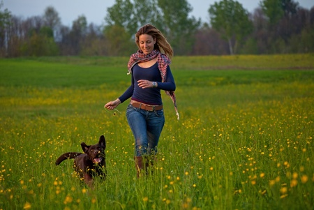 young girl run in the park with a dog