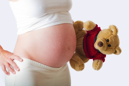 Pregnant woman from the profile with a teddy bear photo