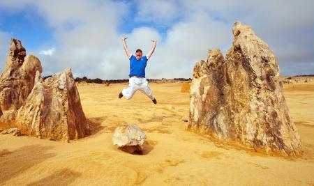 Man jumps in Pinnacles desert, western Australia Standard-Bild