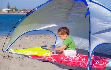 Baby under a beach shelter