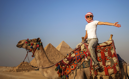 Girl on the camel in front of the Pyramids