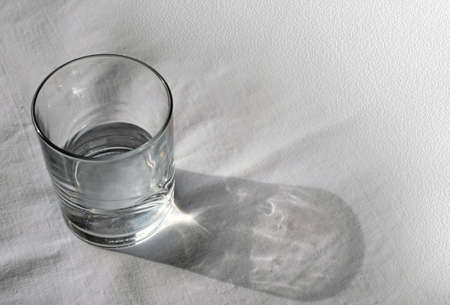 quench: Transparent glass cup with clean water on a light background