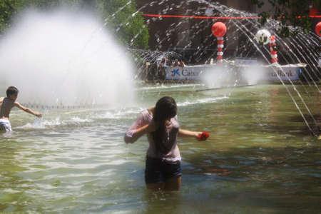 het meisje met natte kleren en gekleurd met wijn in een fontein in Pamplona voor de San Fermin dagen - voor redactioneel gebruik