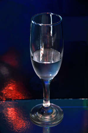 gleam: tall wineglass with clear drinks on a dark background with a red gleam