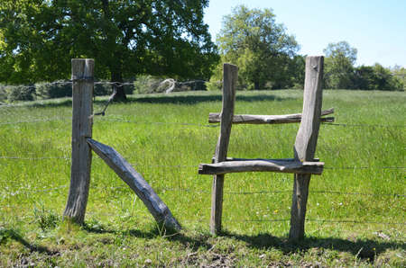 fencing wire: wooden crossing over a barbed wire fencing on private property