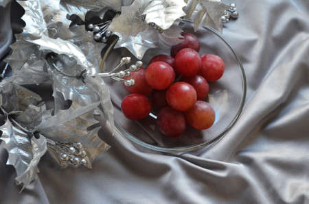 silvery Christmas tree branch on a satin gray background and twelve grapes on a transparent plate