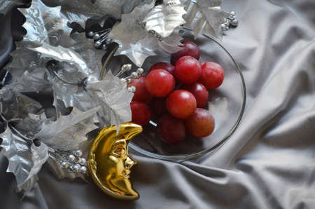 silver Christmas tree branch on a satin gray background,  twelve grapes on a transparent plate and the Christmas Toy Crescent