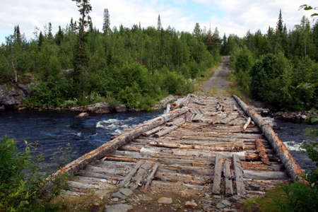 Old wooden bridge over river in Rissian forest