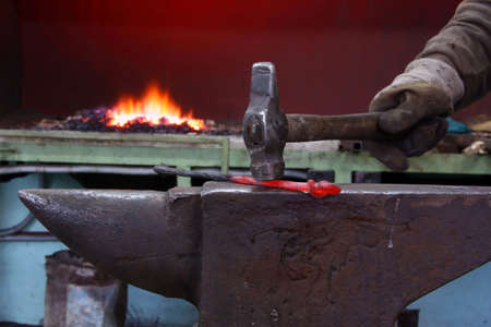 The hand of the smith strikes a hammer on the heated metal on an anvil against fire photo
