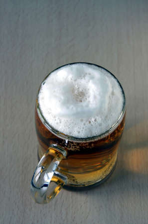 The full glass with foaming beer costs on a wooden table  The top point of shooting