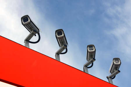 Four observation cameras on a red roof against the blue sky.