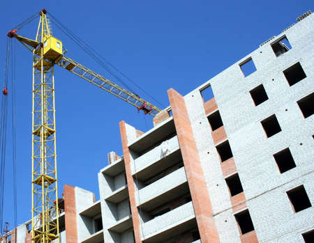Building - the crane near the under construction brick house Stock Photo