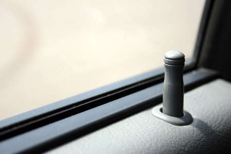 Fragment of an automobile door - the button, the panel and glass. Shallow depth of field. Focus on the button. Stock Photo