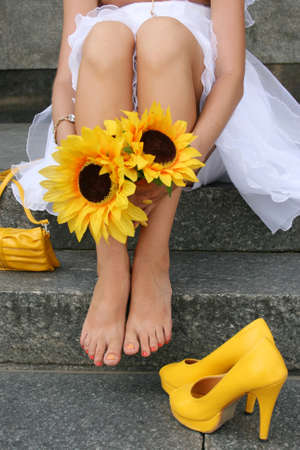 foot model: Yellow shoes and handbag behind at the feet of the bride, who is sitting and holding hands in sunflowers Stock Photo