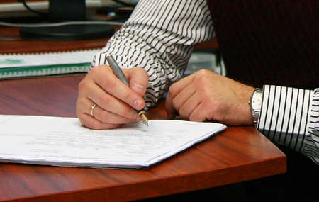 parer: The man signs the document. In a picture the hand with pen and a sheet of paper on a table is visible
