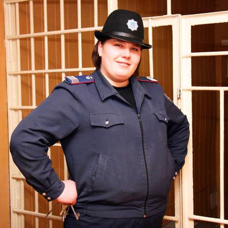 warden: Un guardi�n de prisi�n femenina en uniforme con las llaves en su posici�n de mano contra el tel�n de fondo de celos�a de prisi�n