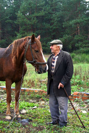 An old man standing next to a horse near the destroyed building on a background of forest