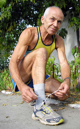 An elderly man in a T-shirt and athletic shorts squatted down and tying shoelaces on sneakers       Stock Photo