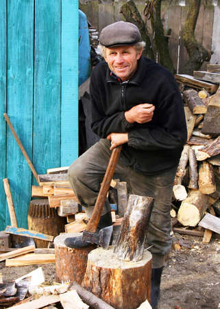 A man stands next to the deck leaning on an axe Stock Photo