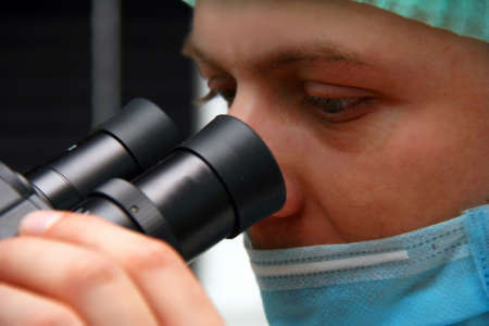Close-up face of the doctor who is looking into microscope Stock Photo - 11556846