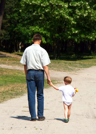 Father and son walking in the park summer day