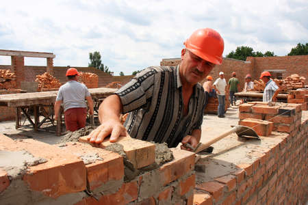 A man puts a brick in the construction